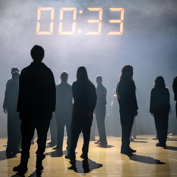 Flertalet skådespelare står med ryggen mot kameran, med ansiktet vänt mot en stor klocka på väggen.