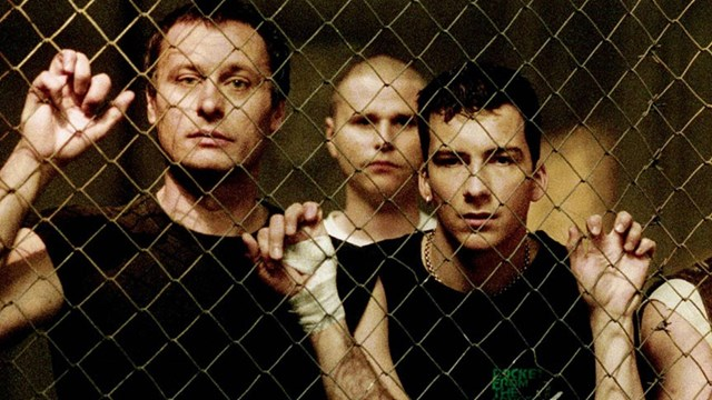 Michael Nyqvist, Shanti Rooney och Jakob Stefansson ståendes bakom ett gallerstaket.