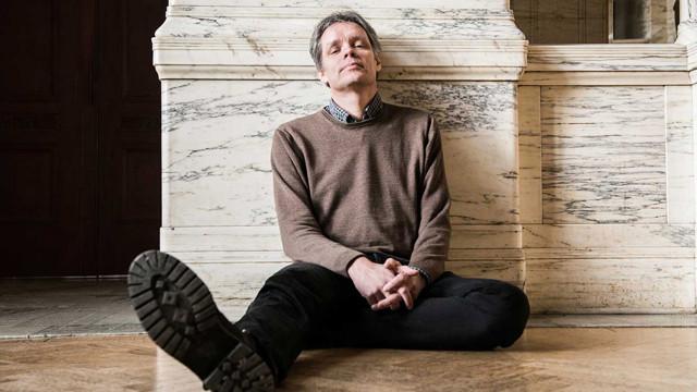 Ulf Danielsson sitter på golvet i Marmorfoajén.