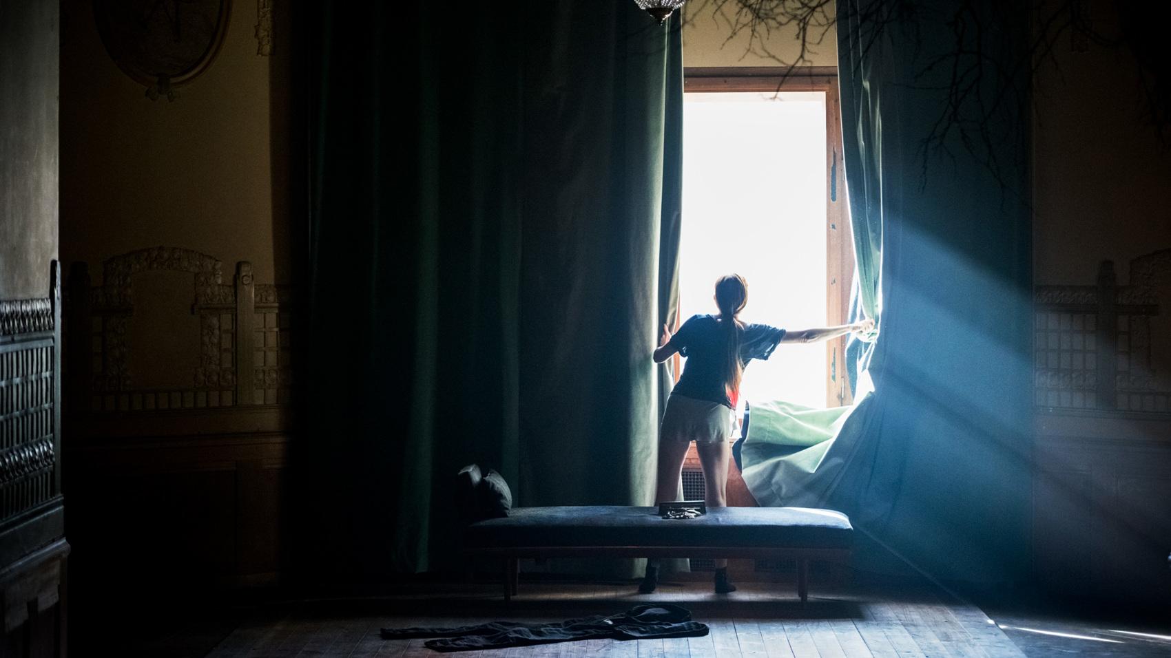 En kvinna drar undan gardinerna från fönstret i Lejonkulan.