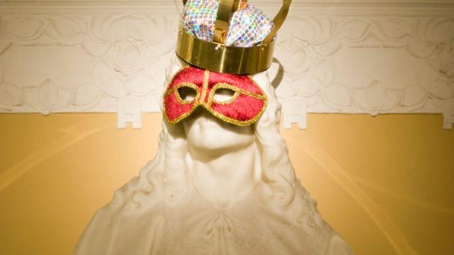 En staty klädd med röd teatermask och kungakrona.