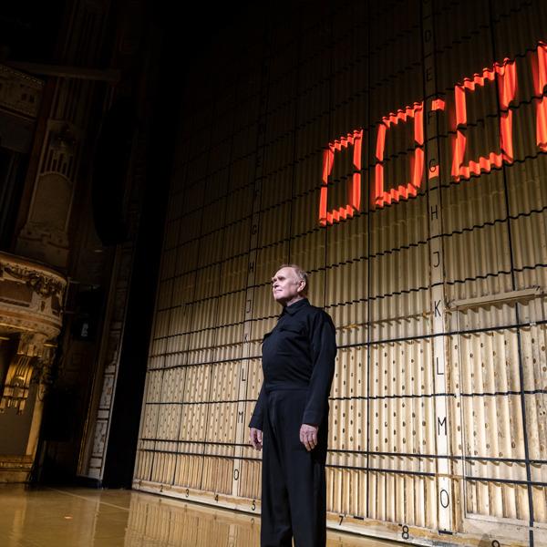 Pierre Wilkner ståendes ensam på Stora scenen framför järnridån.